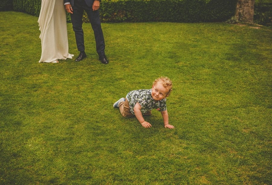 The bride and grooms son crawls along the grass in the gardens at Abbey House