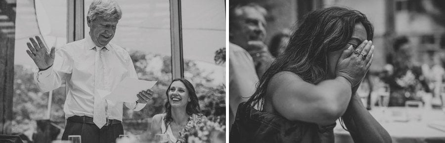 A wedding guest holds her hands in her face and laughs as the brides father delivers his speech