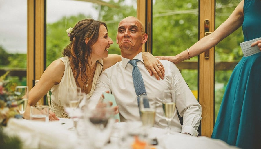 The bride places her arm around her husband and laughs