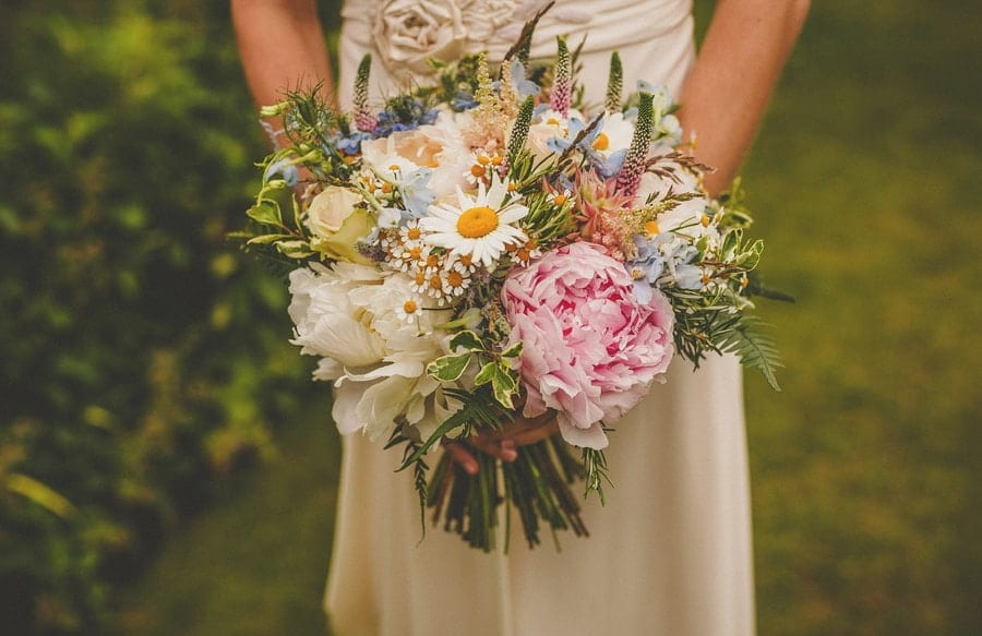 The bride holds her flower bouquet with both hands