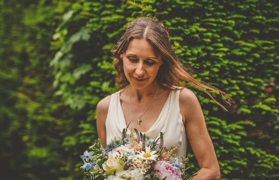 The bride looks down on the floor and holds her wedding bouquet