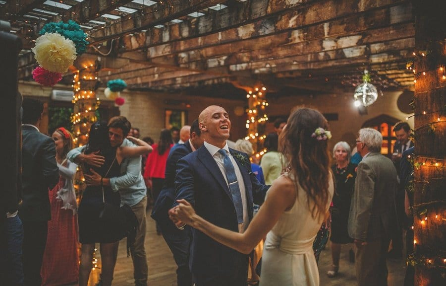 The groom holds his brides hands on the dancefloor and smiles at her