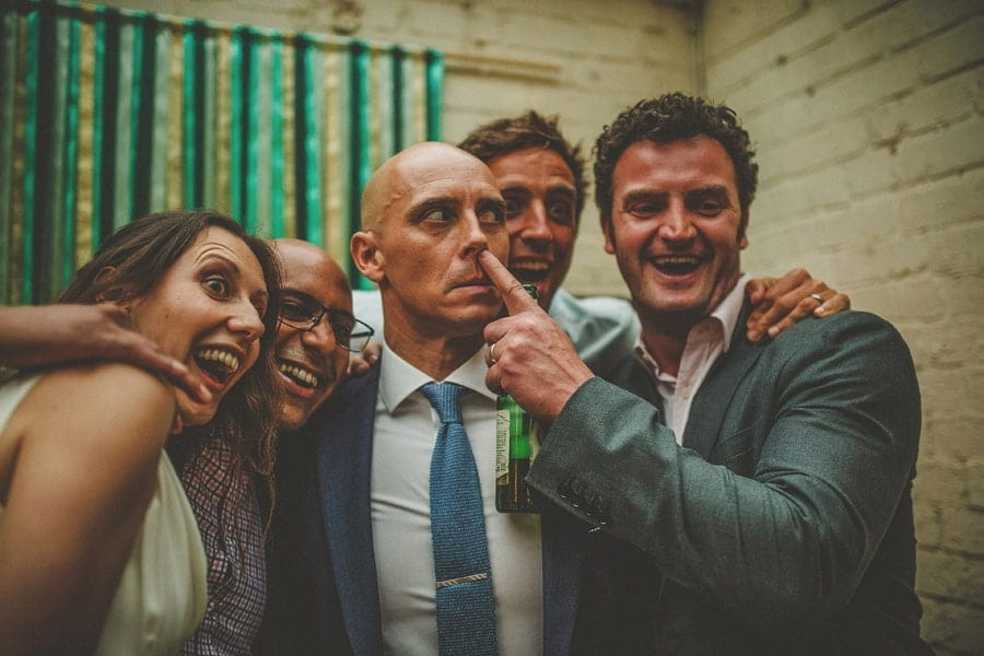 A wedding guest places his finger to the grooms nose and laughs as they pose for photographs in the photo booth