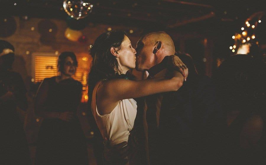 The bride kisses the groom on the dancefloor
