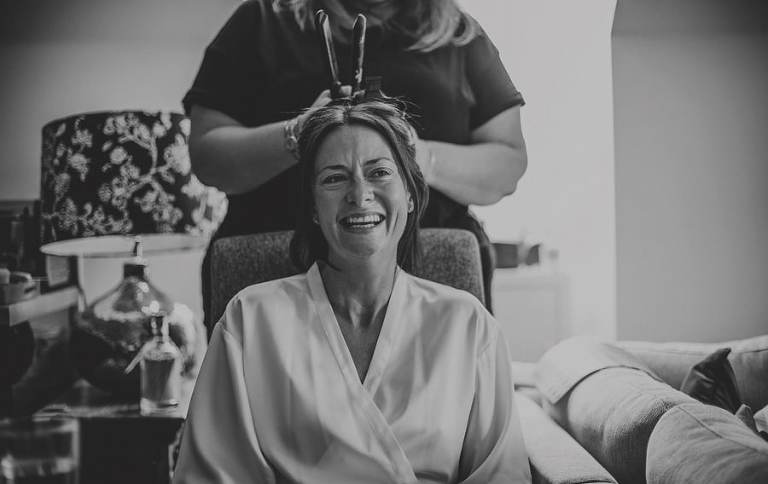 The bride laughs as her hairdresser ties her hair back