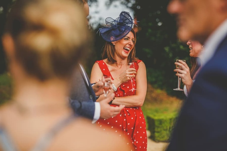 A wedding guest laughs with friends