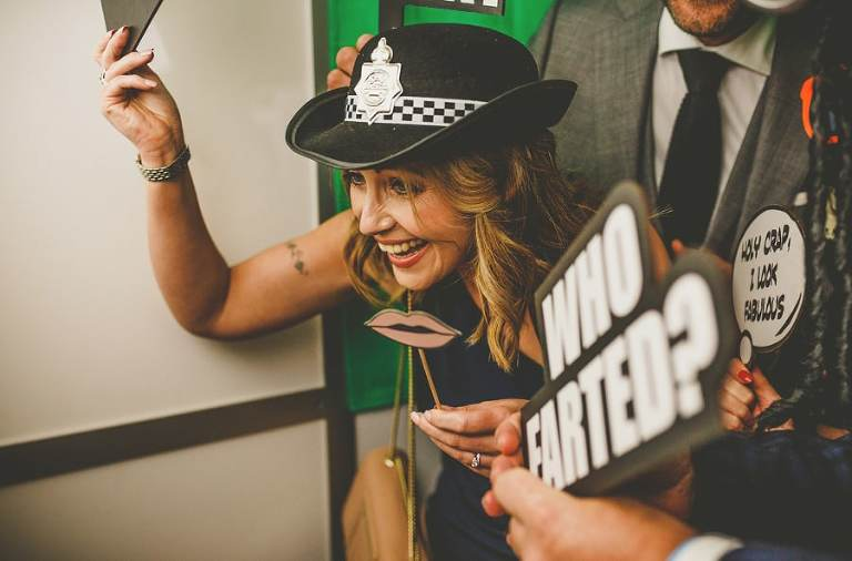 A wedding guest poses for a photograph in a photo booth in Clifton, Bristol