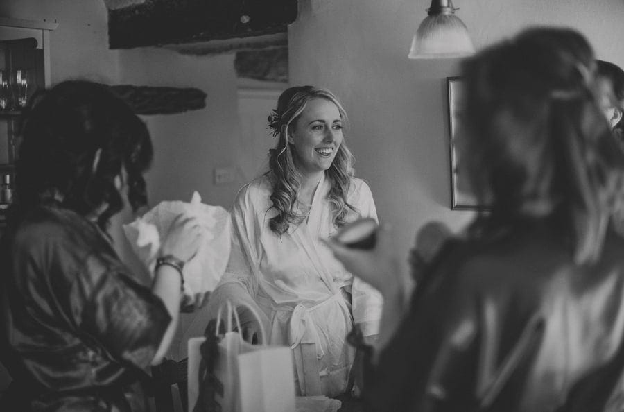 The bridesmaid smiles as she watches her bridesmaids open gifts in the kitchen