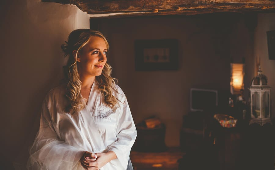 The bride poses for a photograph as she looks outside into the front garden of the kitchen
