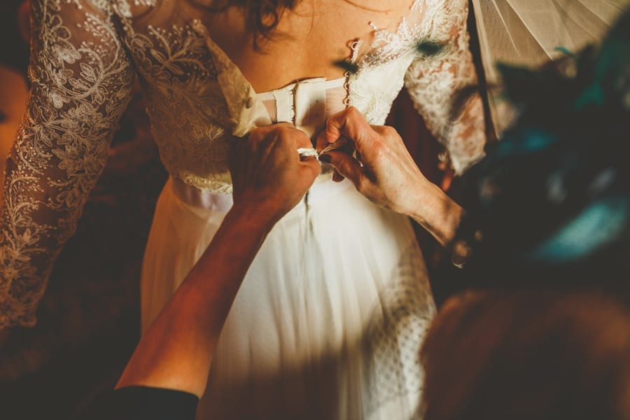 The mother of the bride ties the back of her daughters wedding dress in one of the bedrooms of the cottage