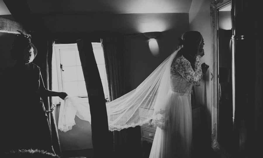 The bridesmaid puts on earrings as she looks in the mirror in the bedroom