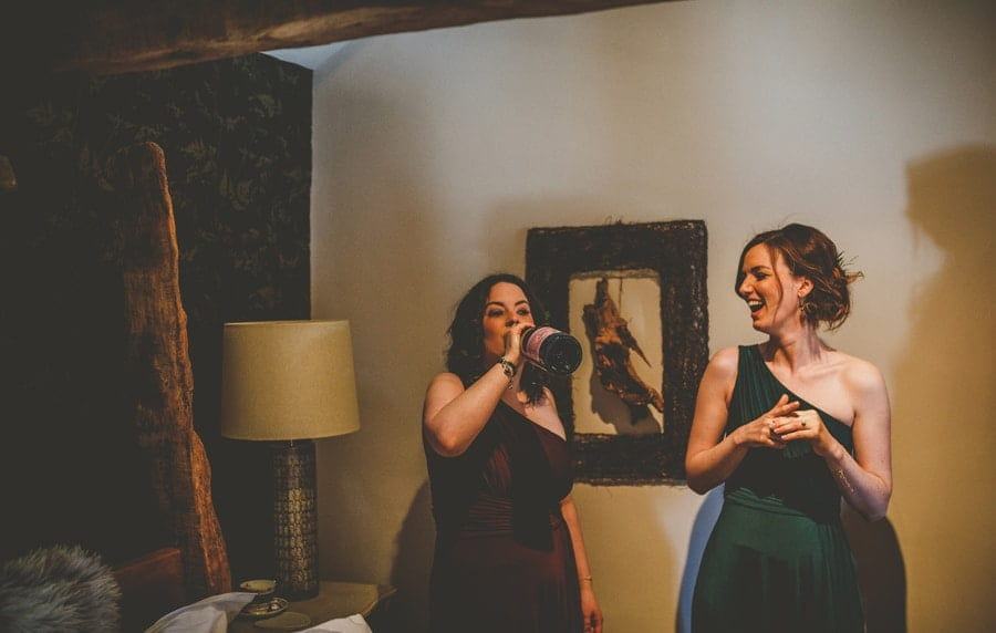 A bridesmaid puts a bottle of champagne to her mouth as her friend standing next to her laughs