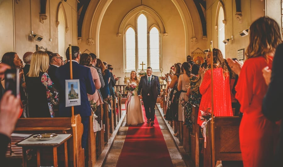 The bride and groom walk down the aisle of the Church together as wedding guests stand up and clap their hands