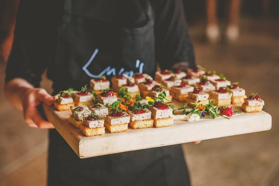 A member of staff from Eden Barn holds a wooden board of canapes