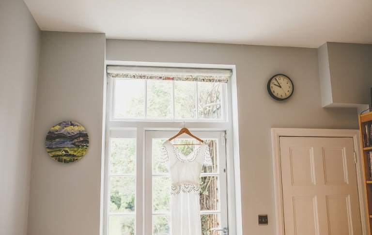 The brides dress hangs from a window ledge in the kitchen of the brides house