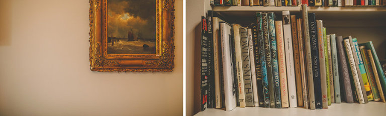 Books on a bookshelf and a framed oil painting hangs on a wall