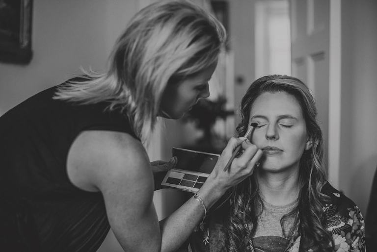 The makeup artist applies make up to a bridesmaid sat on a chair