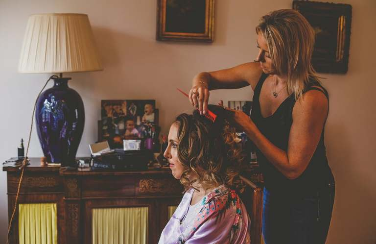The hairdresser combs the bride's hair