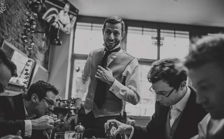 An usher stands up and smiles at the groom in the Kings Arms public house in Fulham