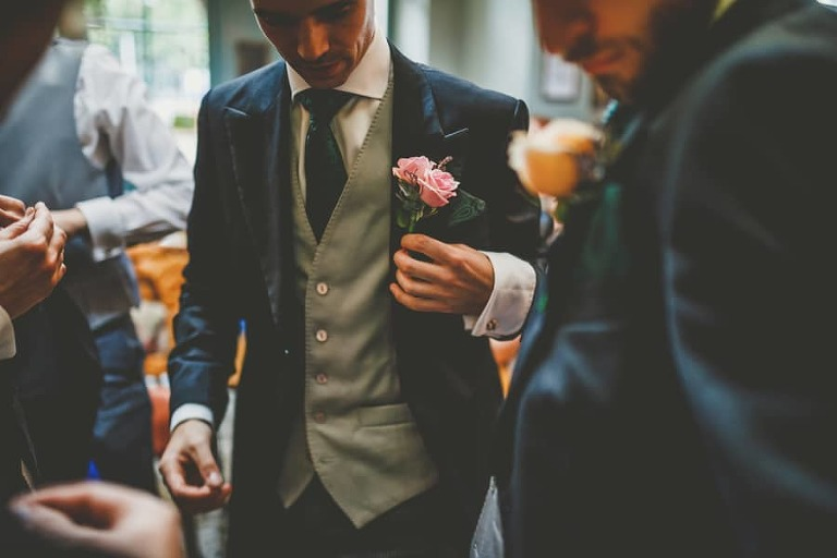 The groom places a flower on the breast pocket of his suit
