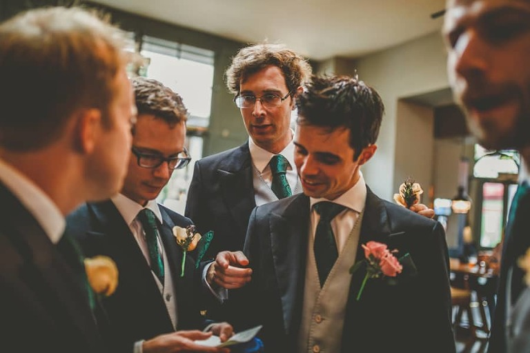 The groom looks at a list written by the best man