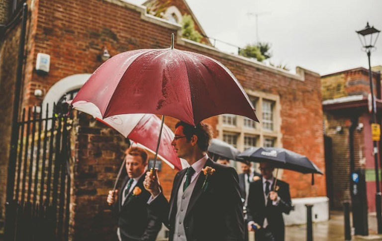 The ushers and the groom hold umbrellas and walk towards the Church