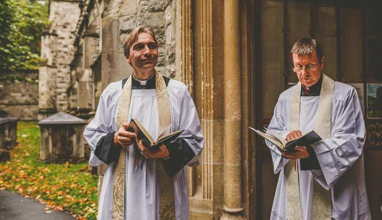 The vicar holds a bible and waits for the bridal party outside the Church at Fulham Palace