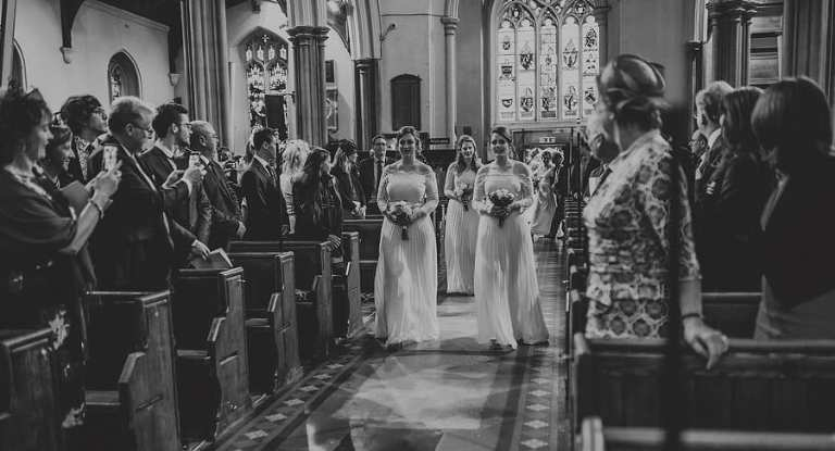 The bridesmaids walk up the aisle of the Church together carrying their bouquets