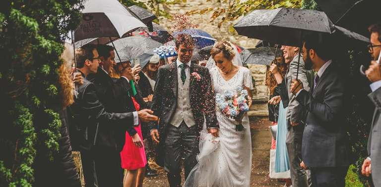 Confetti is thrown in the air as the bride and groom walk out of the Church together