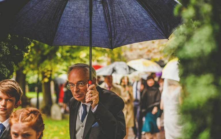 A wedding guest holds an umbrella and walks through the gardens of the Church
