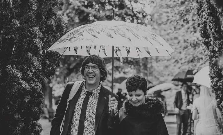 A man holding an umbrella and a lady at his side smile as they walk through the gardens of the Church