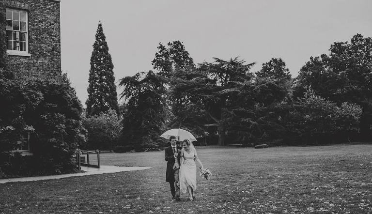 The bride and groom walk through the gardens at Fulham Palace