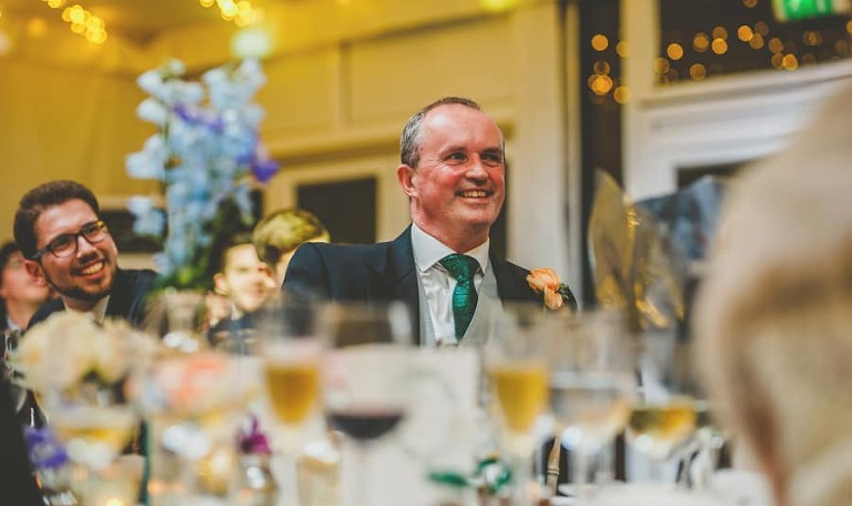 The grooms father laughs as he sits at the table and listens to the best mans speech