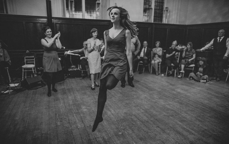 A lady with no shoes on jumps in the air on the dancefloor at Fulham Palace