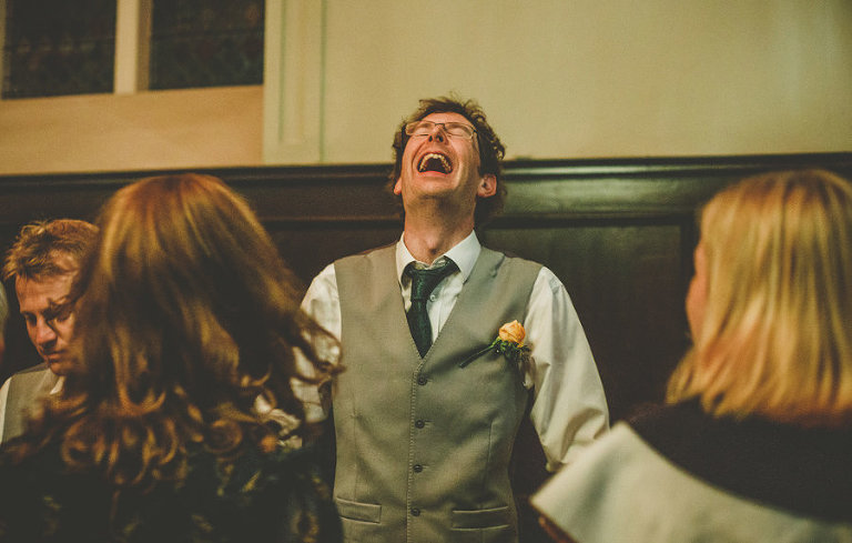 An usher closes his eyes and laughs on the dancefloor at Fulham Palace