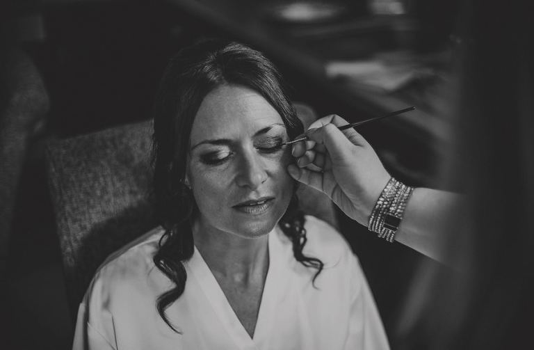 The make up artist applies eye liner to the bride