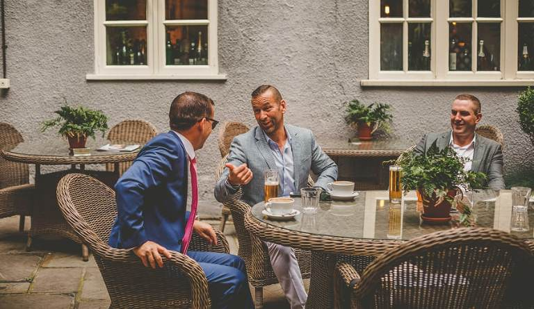 The groom and his ushers sit outside a cafe and chat to one another