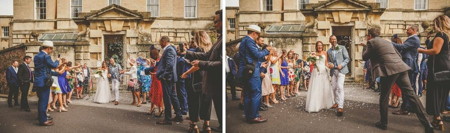 The bride and groom walk out of Goldney Hall wedding venue as friends and family throw confetti