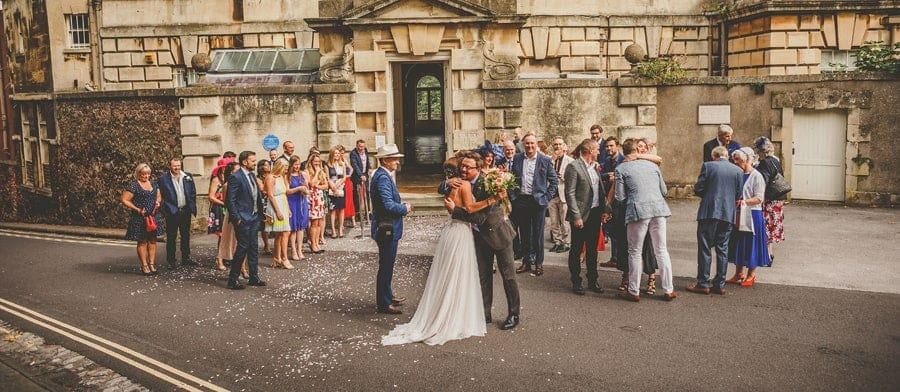 Friends and family congratulate the bride and groom outside Goldney Hall