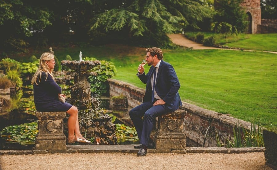 A wedding guest sits on a wall and drinks champagne