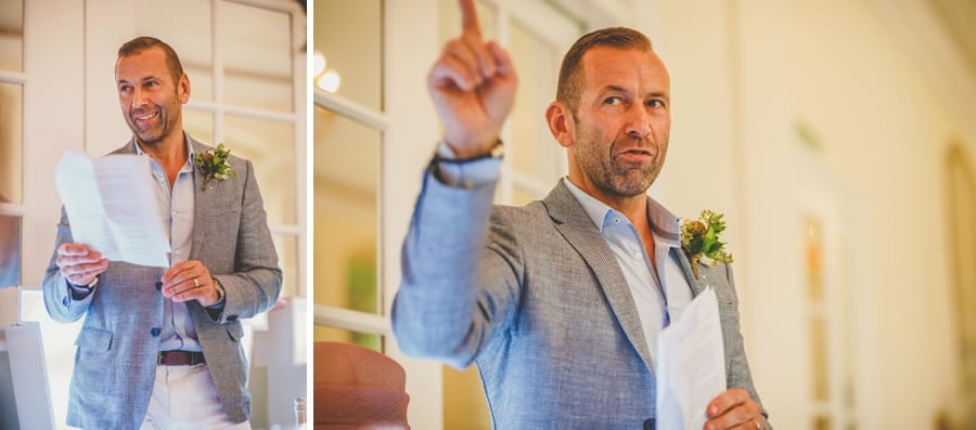 The groom points to the ceiling and delivers his speech to the wedding party
