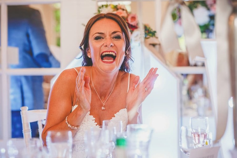 The bride claps her hands and laughs at her husband's wedding speech