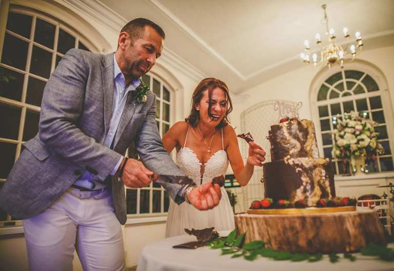 The bride picks up chocolate from the table as her husband cuts the cake