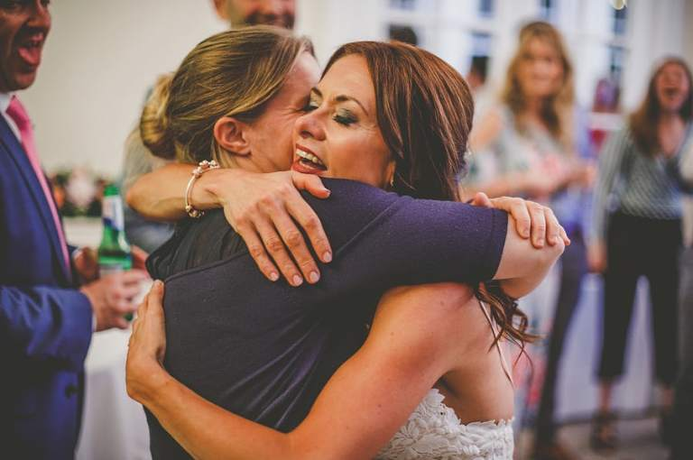 The bride puts her arms around her friend on the dancefloor at Goldney Hall in Clifton
