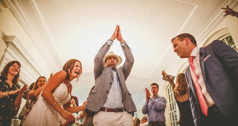 The groom puts his arms in the air as the wedding guests watch on the dancefloor