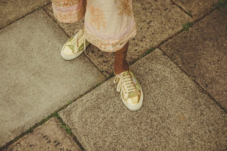 A wedding guests gold coloured shoes
