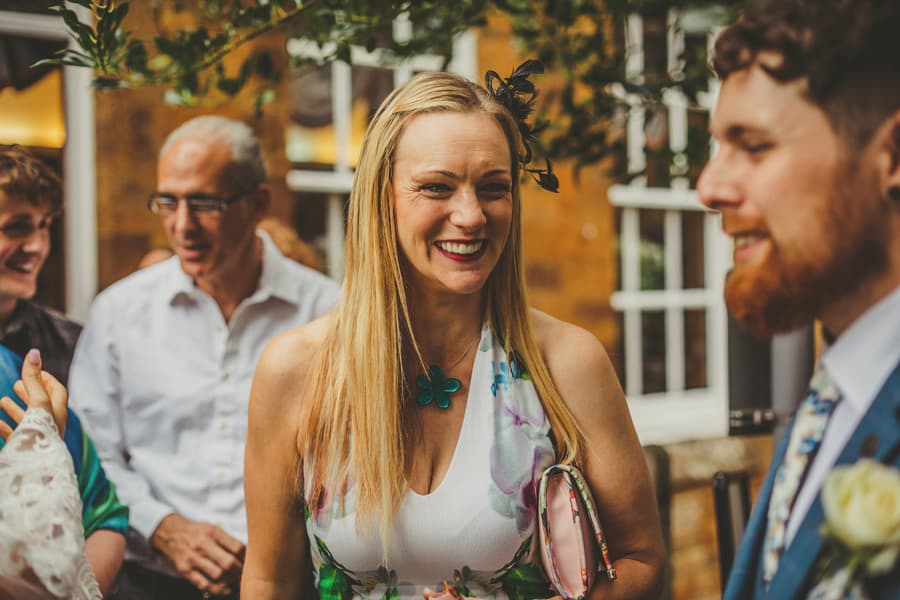 A wedding guest talks to the groom