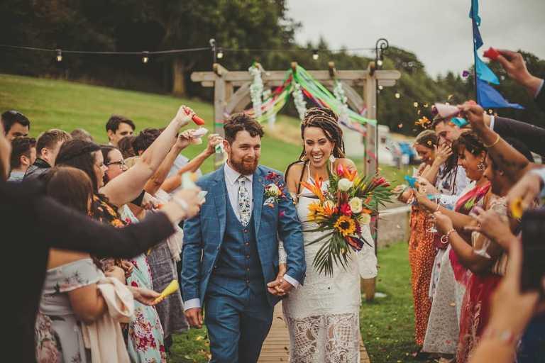 The bride and groom walk into Hadsham Farm as wedding guests throw confetti over them
