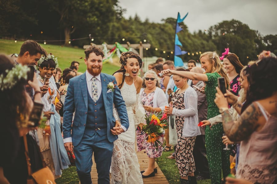 The bride is startled when she is covered in confetti holding the grooms hand at Hadsham Farm