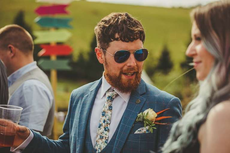 The groom talks to a wedding guest
